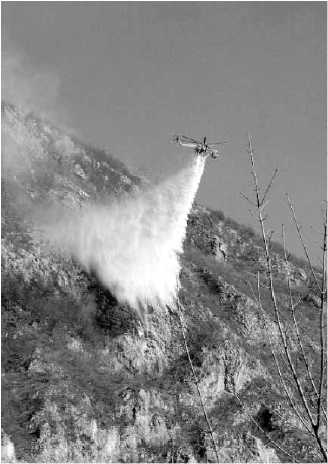 Un elicottero in azione ieri mattina sopra il monte Corno per spegnere l'incendio appiccato dai piromani (foto Fronzi)