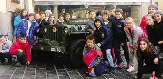 Un gruppo di alunni a Gandino con la jeep Willys