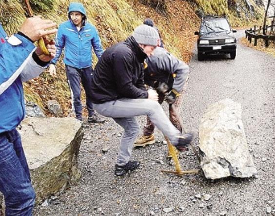 Alcuni volontari rimuovono i massi precipitati sulla strada