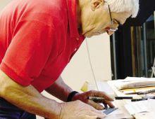 Il fotografo e artista Bepi Rottigni all'opera mentre riproduce gli antichi manufatti